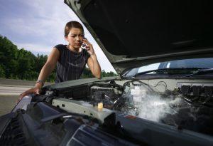 Femme au téléphone et voiture qui fume