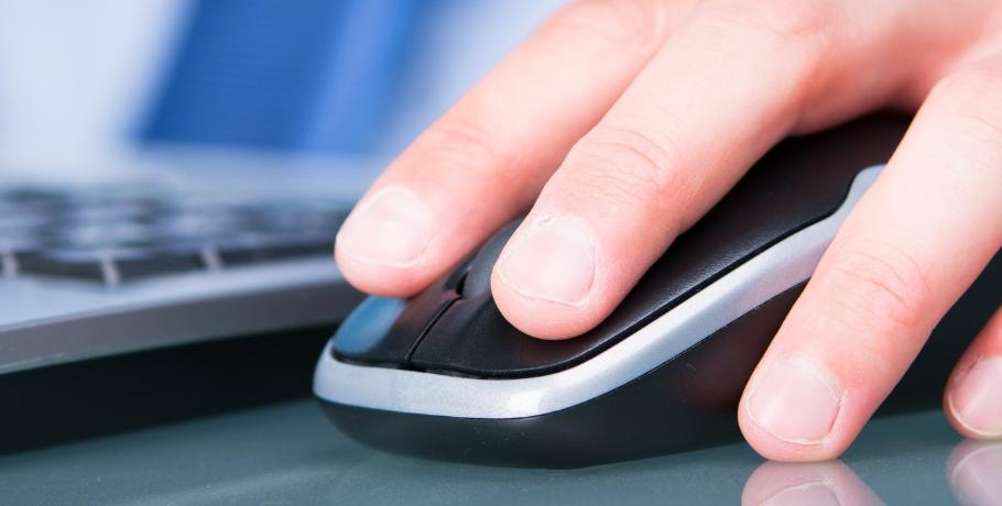 Une main sur une souris d'ordinateur