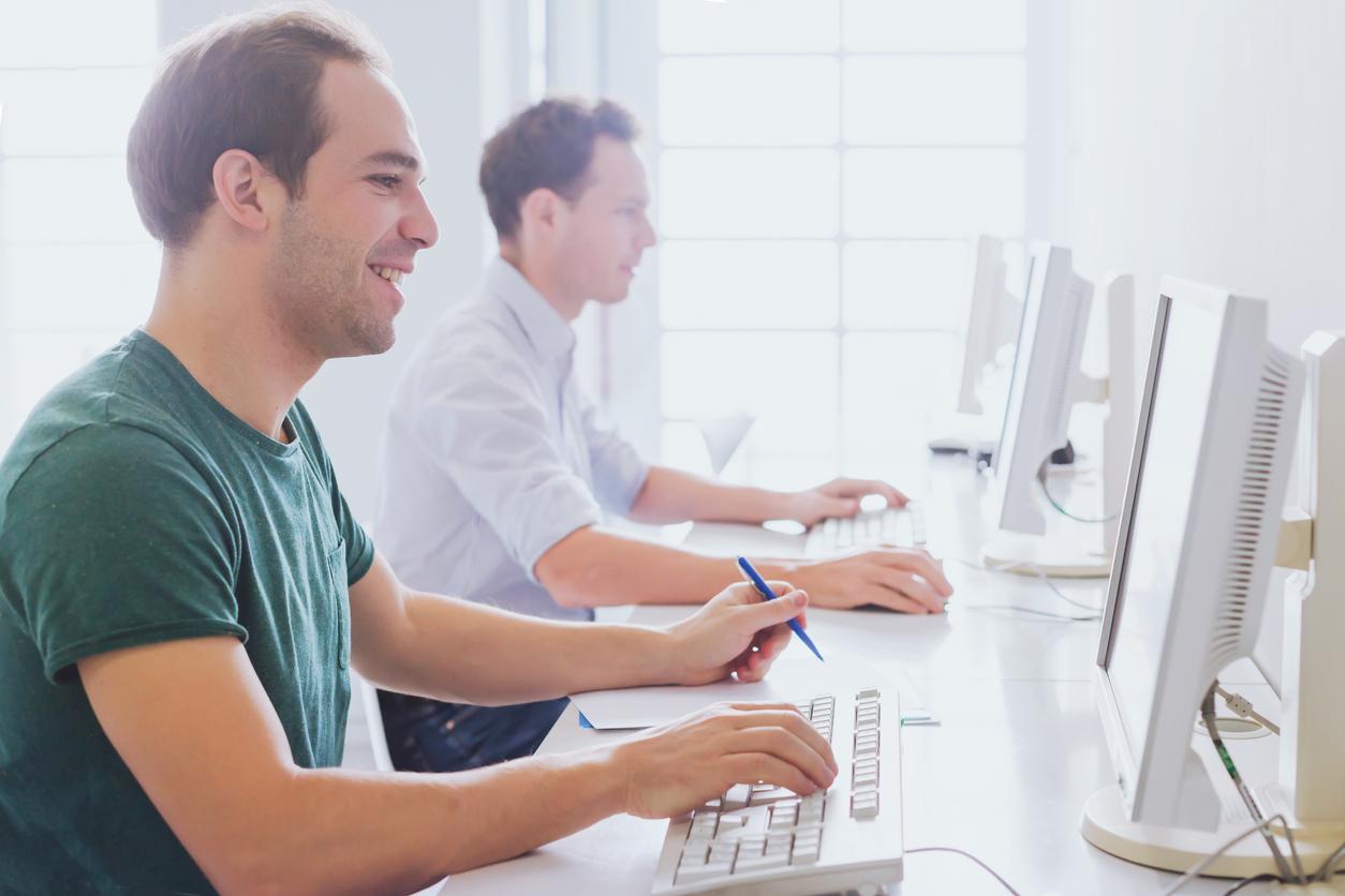 Deux hommes passant l'examen du code code sur des ordinateurs