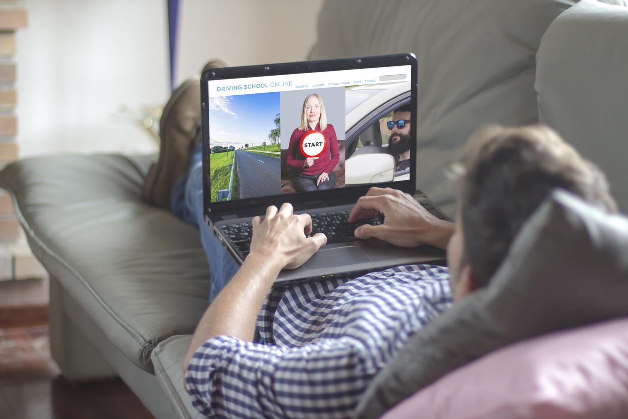Un homme allongé sur son canapé avec son ordinateur sur lui effectuant son code