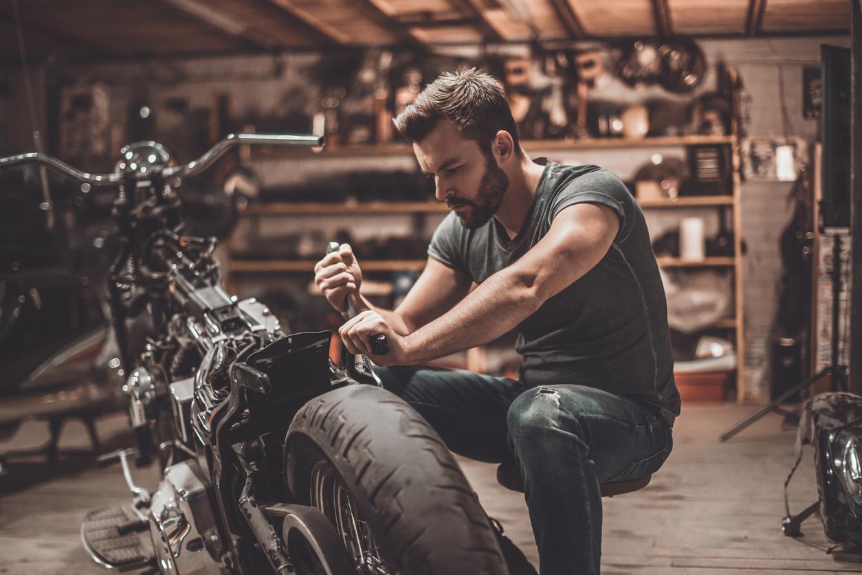 Un homme réparant sa moto