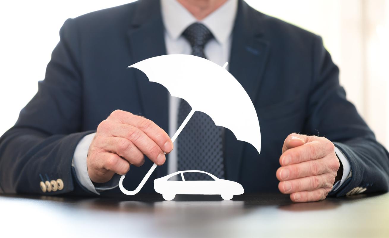 Un homme protégeant une voiture en papier avec un parapluie en papier