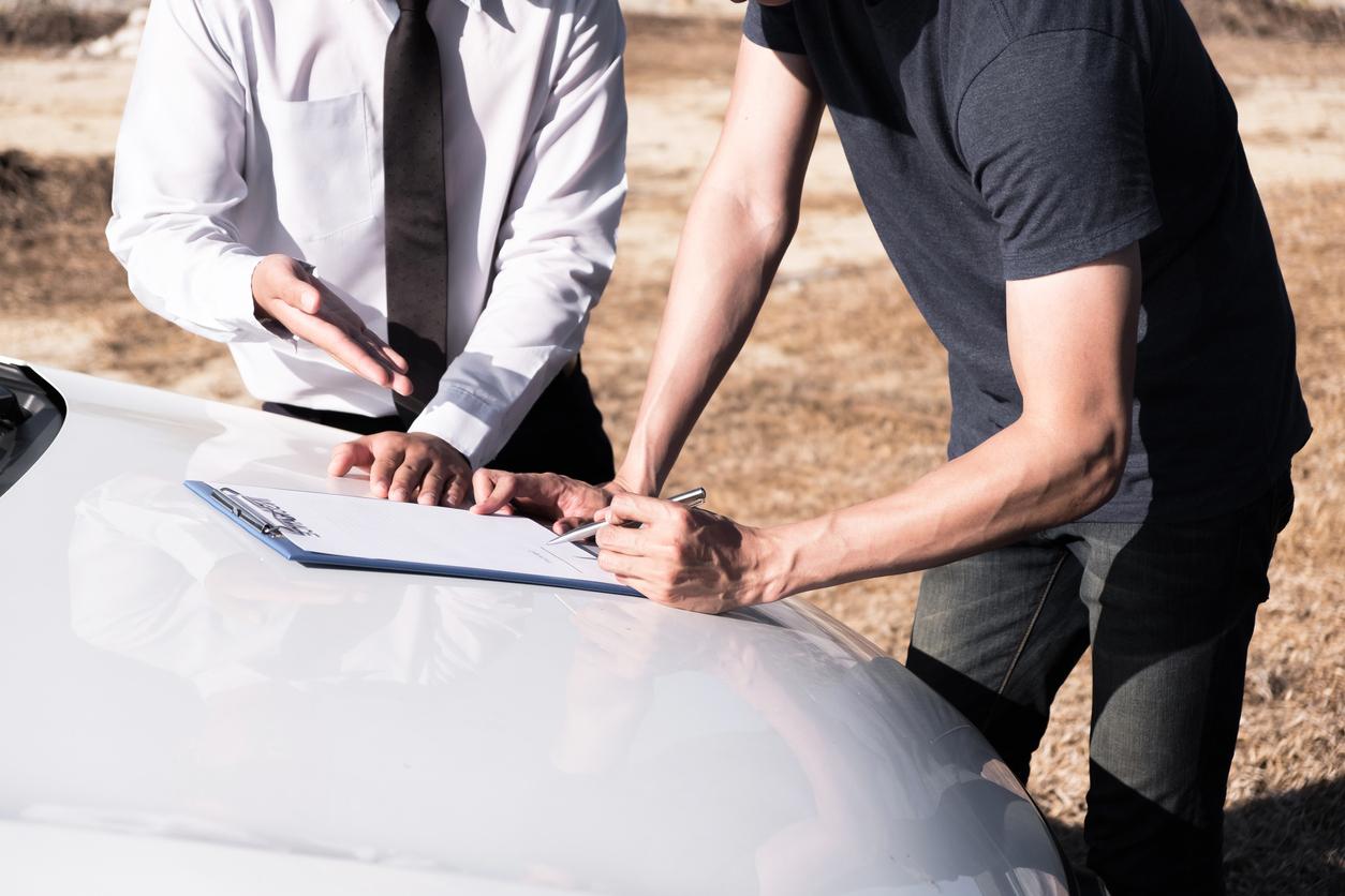 Un homme entrain de remplir un papier d'assurance sur une voiture avec un vendeur à coté