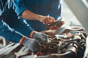 Deux garagistes contrôlant la batterie d'une voiture