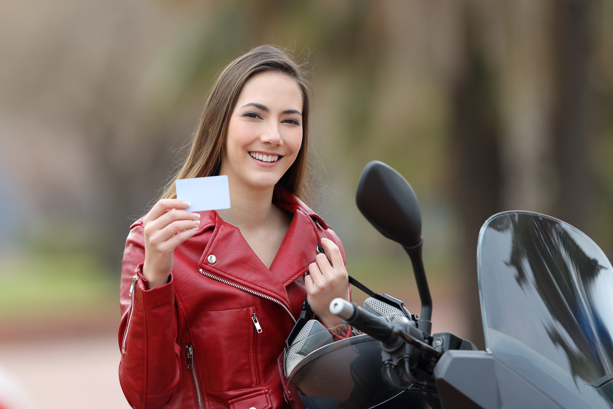 Une femme sur sa moto avec son permis à la main