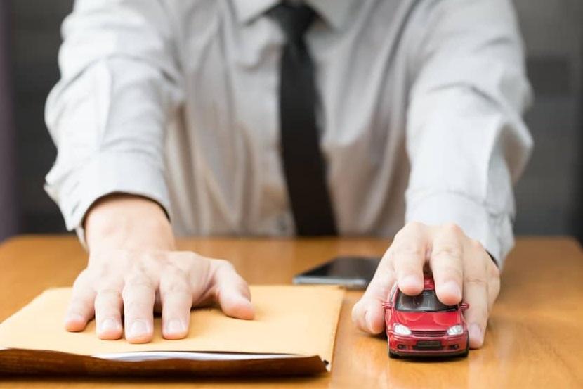 homme en costume donne papiers voiture rouge miniature